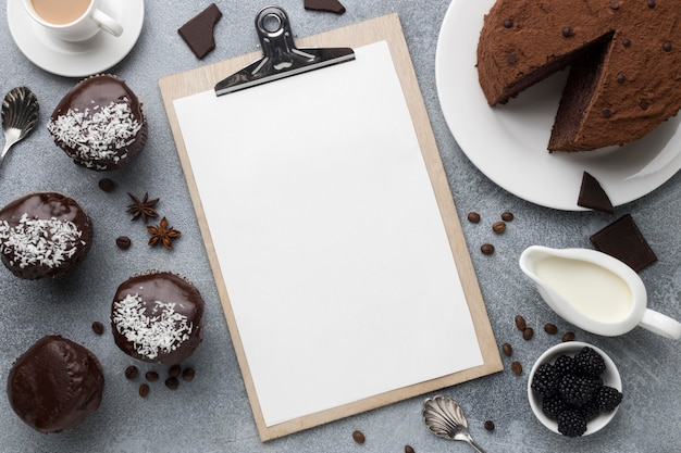 Alto angolo di torta al cioccolato con blocco note e altri dolci
