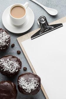 Alto angolo di dolci al cioccolato con caffè e blocco note