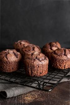 Angolo alto dei muffin al cioccolato sullo scaffale di raffreddamento con lo spazio della copia