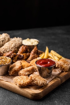High angle of chopping board with fried chicken and sauces with copy space