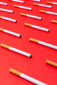 High angle cigarettes on red background