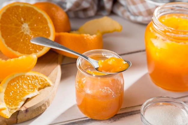 High angle of clear glass jar with orange jam