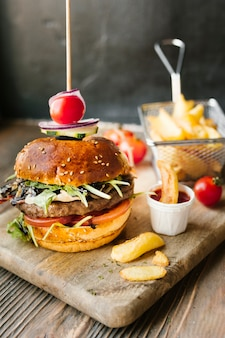 High angle close-up of burger and fries on wooden board