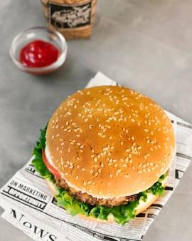 High angle close-up burger on newspaper