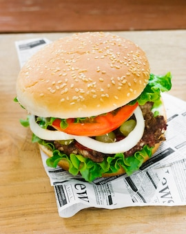 High angle close-up burger on newspaper
