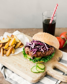 High angle close-up burger with fries on wooden board