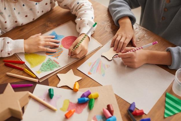 높은 각도는 학교에서 크리스마스 카드를 그리는 동안 모양을 추적하는 어린이의 닫습니다, 복사 공간