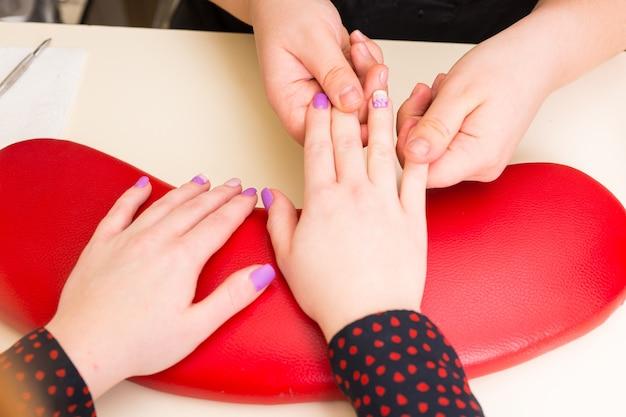 スパの赤い枕の上で休んでいる手で女性のクライアントの手にネイリストマッサージネイルベッドのハイアングルクローズアップ