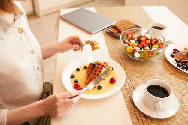 Высокий угол крупным планом неузнаваемой женщины, наслаждающейся вкусным десертом, сидя в одиночестве за обеденным столом