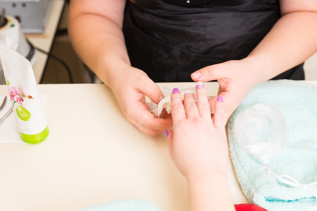 パラフィンワックススパ治療中に女性のクライアントの手からネイリストの剥離乾燥ワックス層の高角度のクローズアップビュー