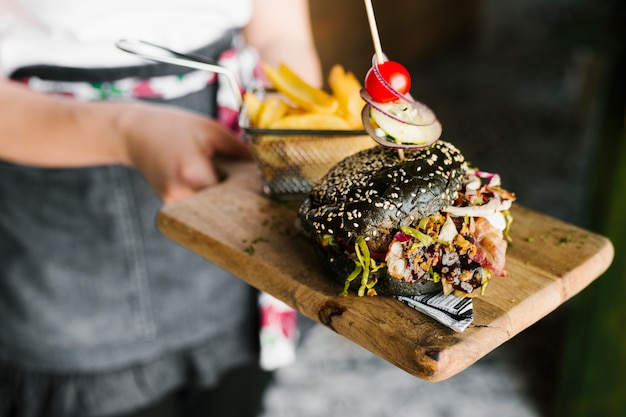 High angle close-up of waiter holding wooden board with black burger and fries