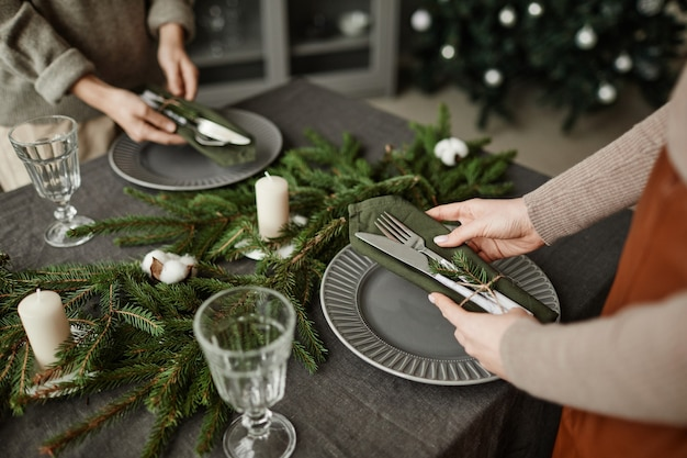 High angle close up of young woman setting up plates on dining table decorated for christmas with fi...