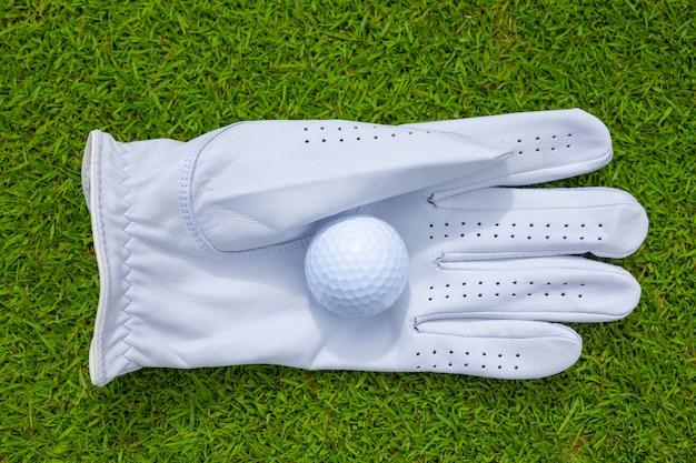 日光の下で芝生の上の手袋のゴルフボールの高角度のクローズアップ