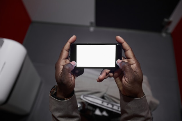 Высокий угол крупным планом афроамериканца, использующего смартфон, сидя на унитазе в общественном туалете, копировальное пространство