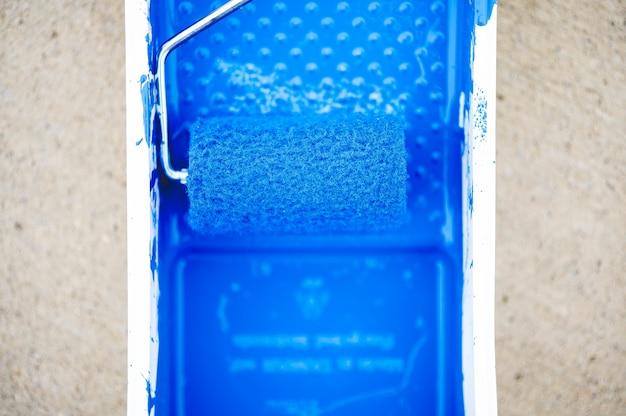 Colpo di primo piano ad alto angolo di vernice blu in un contenitore di vernice con un pennello