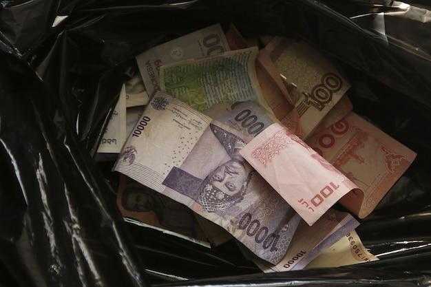 Colpo del primo piano dell'angolo alto di denaro contante in un sacchetto della spazzatura nero