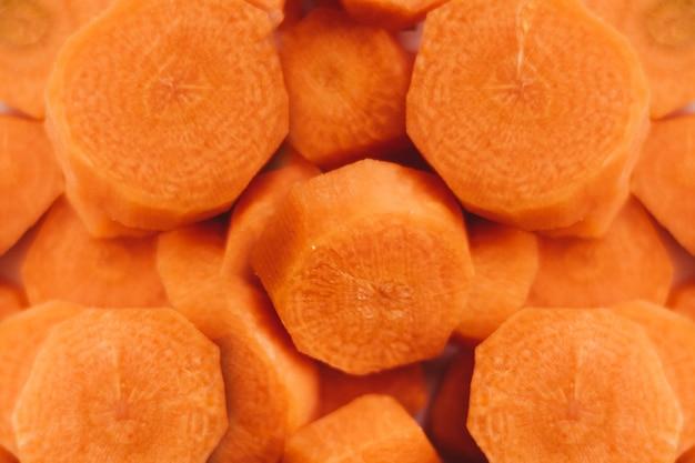 Colpo del primo piano dell'angolo alto di carote crude e affettate deliziose