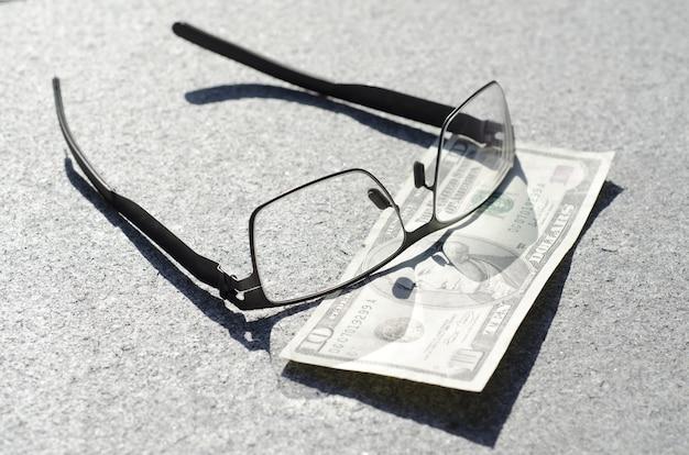 Colpo del primo piano dell'angolo alto degli occhiali su un dieci dollari su una superficie grigia