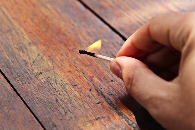 木製の表面に燃えるマッチ棒を持っている人の高角度のクローズアップショット