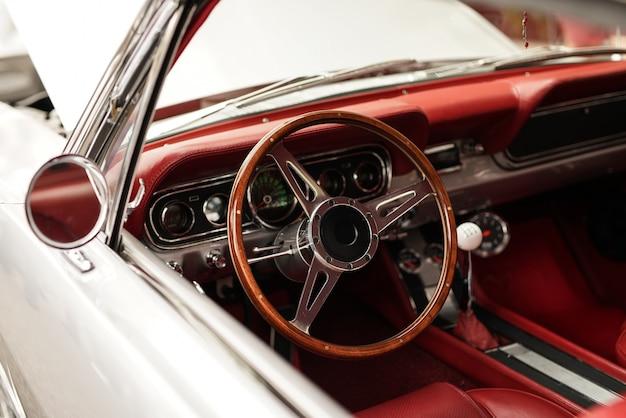 아름다운 스티어링 휠과 흰색 복고풍 자동차의 높은 각도 근접 촬영 샷