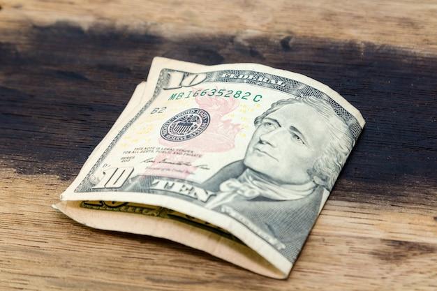 Крупным планом выстрелил американской долларовой банкноты на деревянной поверхности под высоким углом