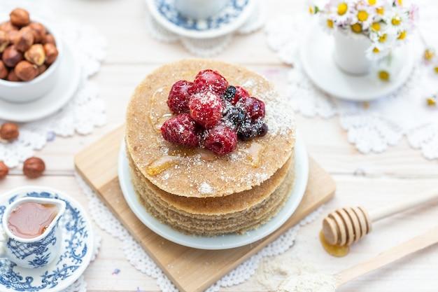 꿀과 딸기와 함께 원시 채식주의 팬케이크의 높은 각도 근접 촬영 샷
