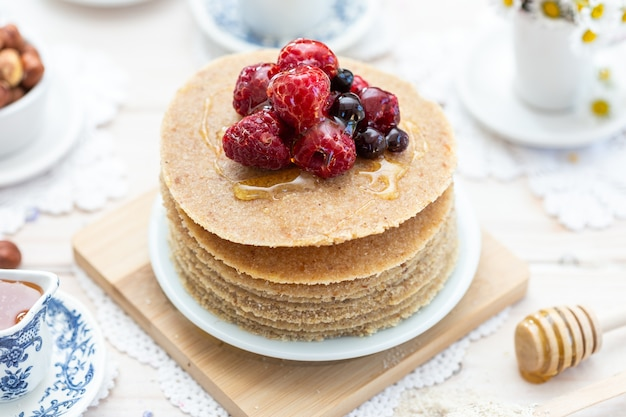 Крупным планом снимок сырых веганских блинов с медом и ягодами под высоким углом