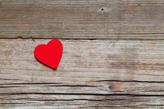 Крупным планом выстрел из красного сердца на деревянной поверхности под высоким углом