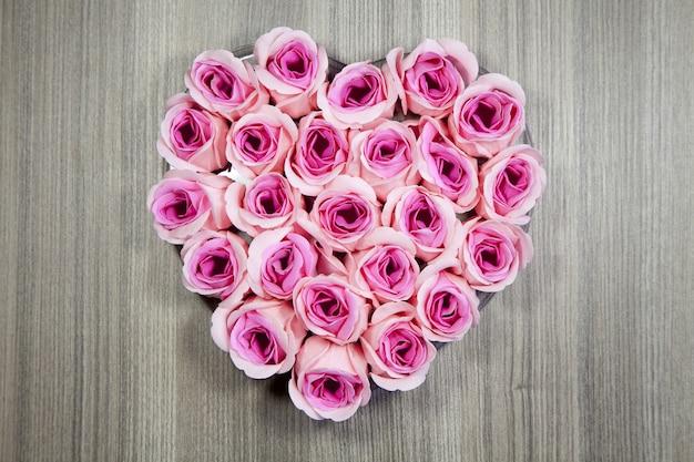 Colpo del primo piano dell'angolo alto delle rose rosa a forma di cuore su una superficie di legno