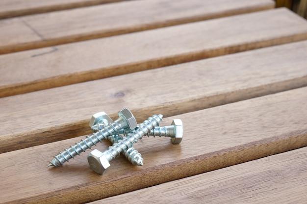 Colpo di primo piano alto angolo di viti su un tavolo di legno