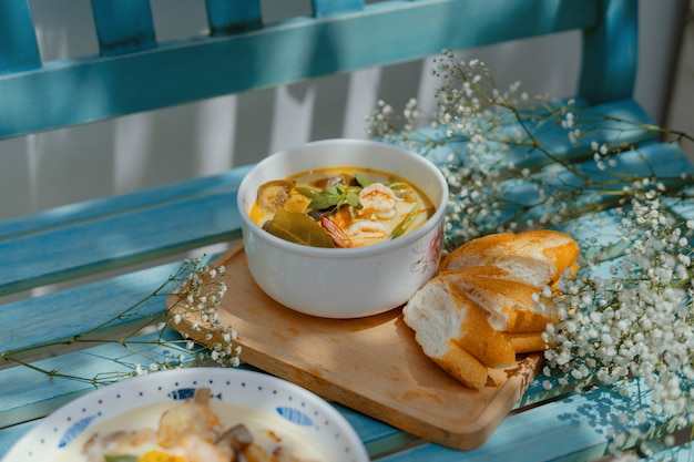 High angle closeup shot of a soup with seafood and vegetables with baguette slices on a blue bench