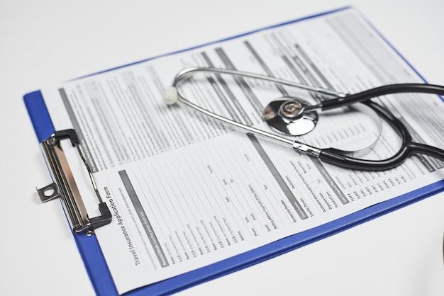 Primo piano ad alto angolo di uno stetoscopio su un documento di domanda di assicurazione di viaggio