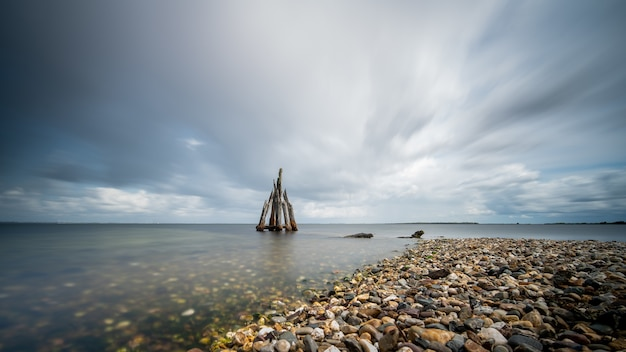 Colpo del primo piano dell'angolo alto di pietre in riva al mare che porta al mare calmo