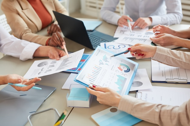 High angle closeup of unrecognizable businesswoman holding data chart with statistics info while planning finance plan during meeting in office