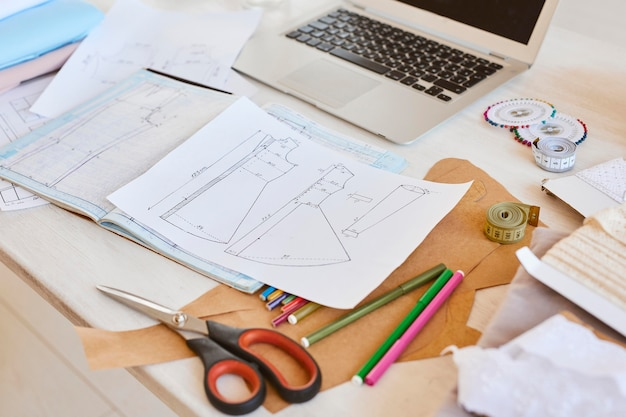 High angle of clothing line plans on table with laptop and scissors in atelier
