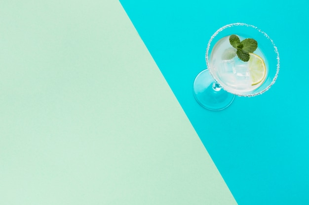 High angle of cocktail glass with copy space and lime