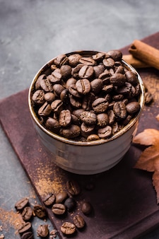 シナモンとまな板の上のカップの高角度のコーヒー豆