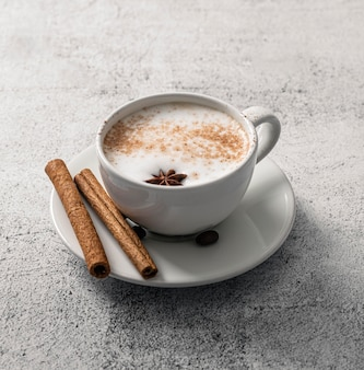 High angle of coffee cup with cinnamon sticks and star anise