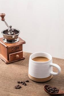 Elevato angolo di macinino da caffè con tazza e chicchi di caffè