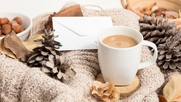 High angle of coffee mug with autumn leaves and pine cones