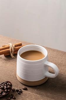 Angolo alto della tazza da caffè con bastoncini di cannella