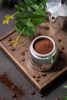 High angle coffee powder in container on wooden board