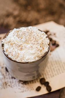 Кофе высокого угла с молоком и взбитыми сливками с корицей
