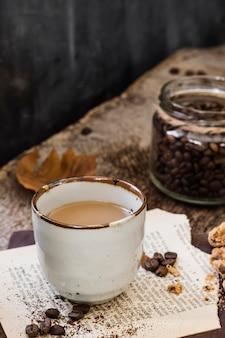 High angle coffee with milk and cofee beans jar