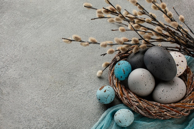 High angle of colored easter eggs in basket with copy space and twigs