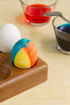 Alto angolo di uova colorate con vernice in bicchieri e cucchiaio per la pasqua