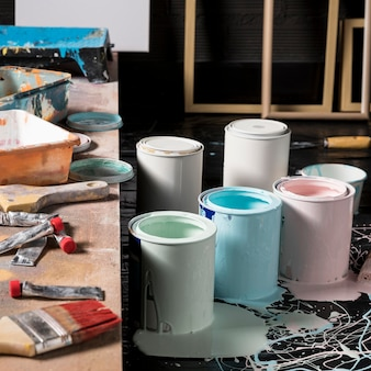 High angle of colored paint cans in studio with frames and brush