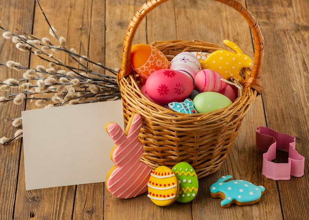 High angle of colorful easter eggs in basket with bunny and paper
