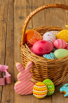 High angle of colorful easter eggs in basket with bunny