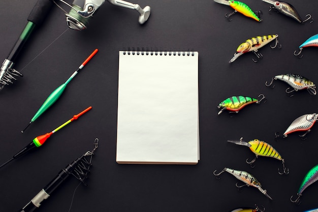 High angle of colorful fishing bait with notepad and rod
